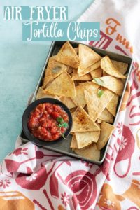 top view of a grey pan filled with air fryer tortilla chips and a salsa plate placed on the inner left side of pan. Grey pan is on top of a colorful kitchen towel