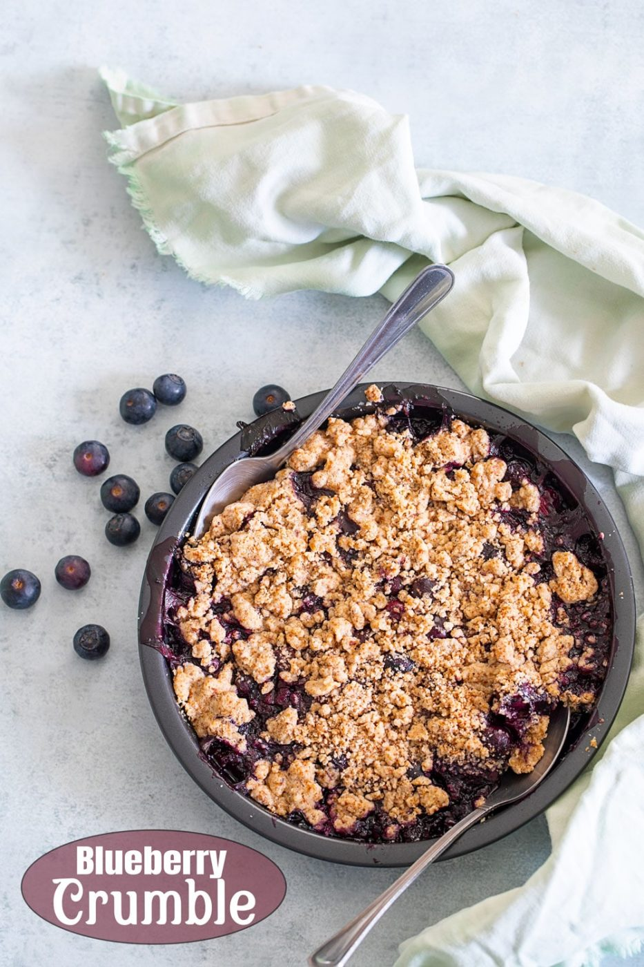 overhead view of a blueberry pie crumble in a pan with a spoon in it. On the side, there are fresh blueberries and light green cloth on the side
