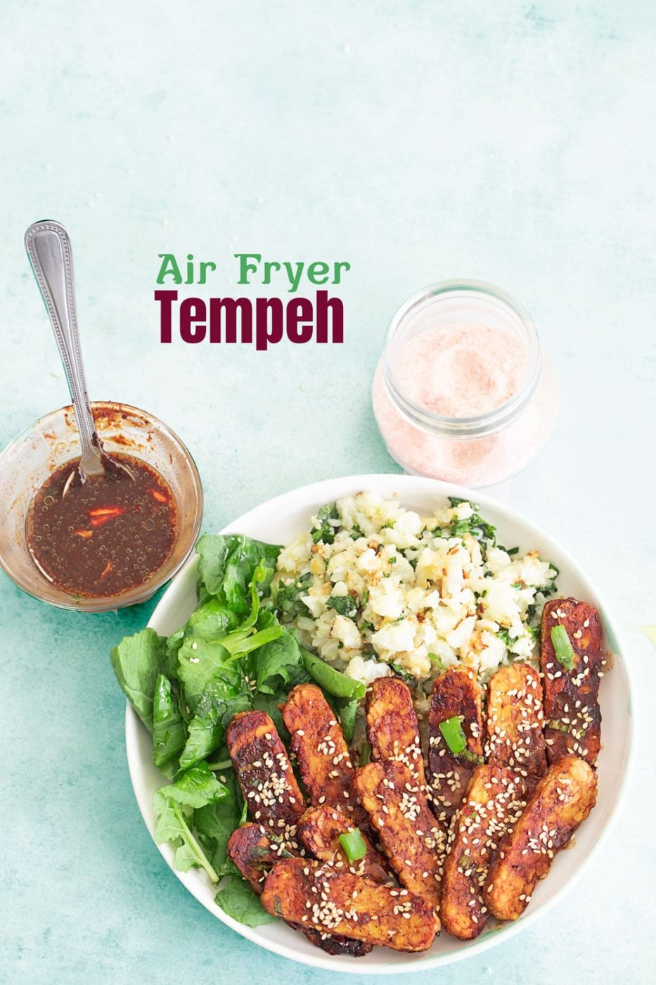 top view of tempeh buddha bowl with a black bean sauce on one side and a glass bottle with salt