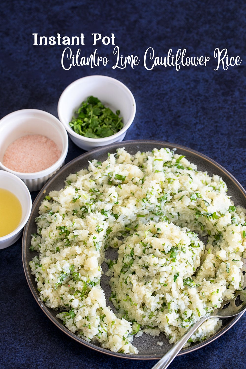 Top view of a grey plate filled with the cauliflower rice arranged in a somewhat spiral design with a side of 3 ramekins